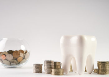 Tooth and jar with coins symbolizing dental insurance