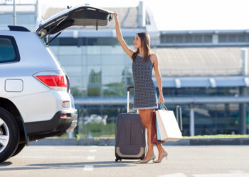 woman at airport car park closing the trunk with suitcase