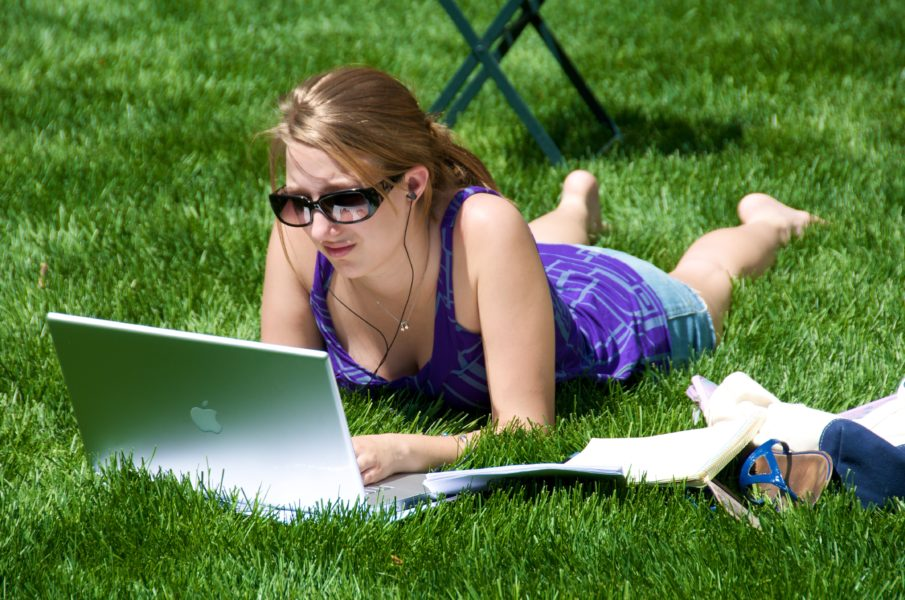 woman laying on the grass studying online on her laptop