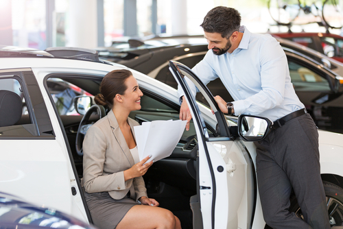 man and woman looking at new car and signing car lease