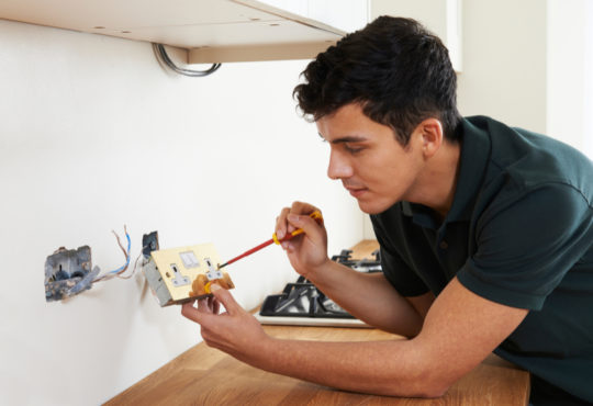 Handsome Electrician Working in House