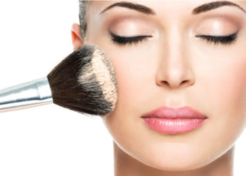 Close up of womens face and brush with make up powder