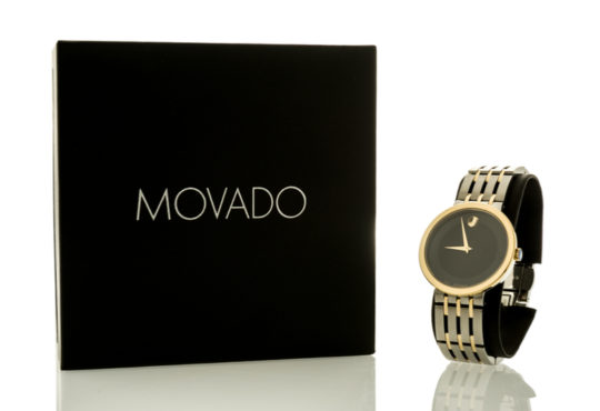 Box labeled Movado with black and gold watch standing beside it