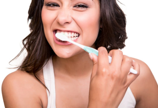 smiling woman brushing her teeth with whitening toothpaste
