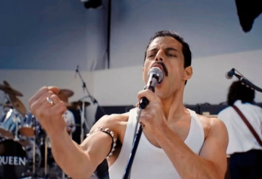 Still of the movie Bohemian Rhapsody with Rami Malek as Freddy Mercury during Live Aid Performance