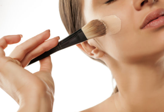 Close up of female face applying liquid foundation with a brush