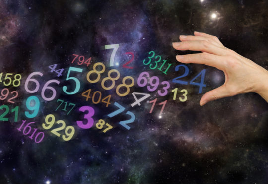 hand and different angel numbers in front of universe background