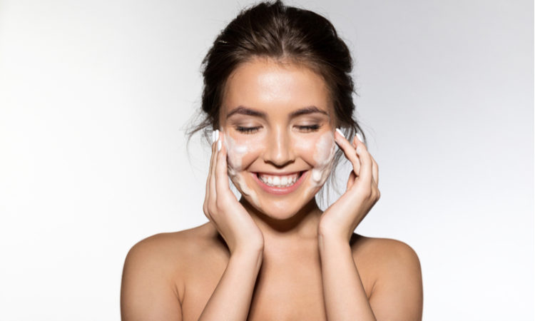 Woman washing her face with face cleanser