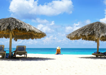 woman sitting on stunning beach in Aruba between parasols