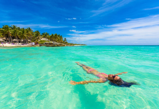 woman swimming in the turquoise sea of Cancun, Mexico