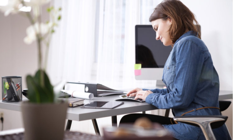 young woman sitting at her desk doing her taxes with calculator, folders and computer