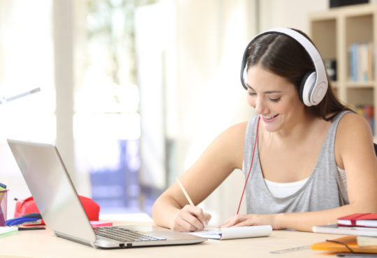 young woman studying on her laptop with headphones at an online college taking notes