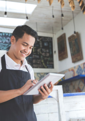 young cafe owner is promoting his business online on his tablet
