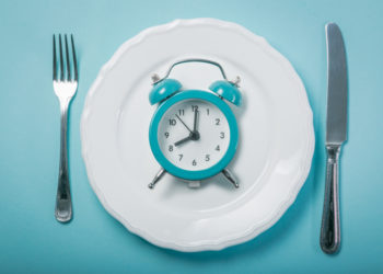 Empty plate with a blue alarm clock on blue background symbolizing the Dubrow diet with intermittent fasting