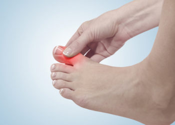 woman with big toe pain holding her big toe