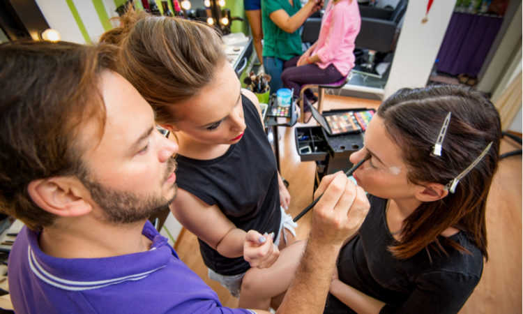 Makeup teacher helping students training to become makeup artist