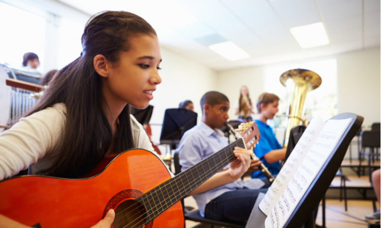 kids playing guitar and other instruments at music school