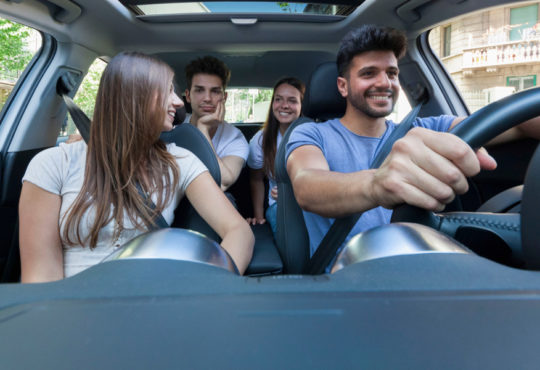 Young people sharing a car and laughing symbolizing car sharing services