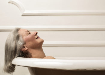 senior woman laying and relaxing in walk-in tub