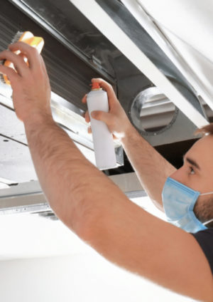 Male technician performing air duct cleaning