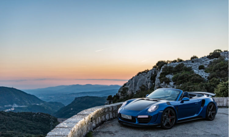 new Porsche 911 parked in front of beautiful skyline and sunset