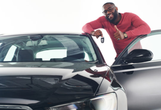 African man showing car keys in near his newly bought vehicle