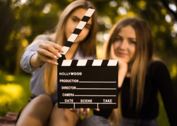 Young women and movie clapperboard symbolizing film school