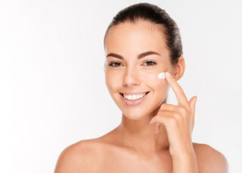 Beautiful young woman applying moisturizing cream on face