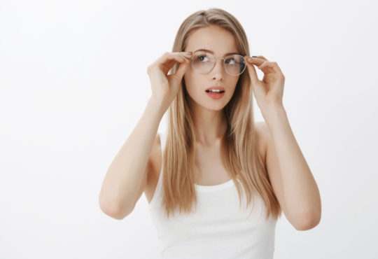 young woman tries on glasses that she purchased online