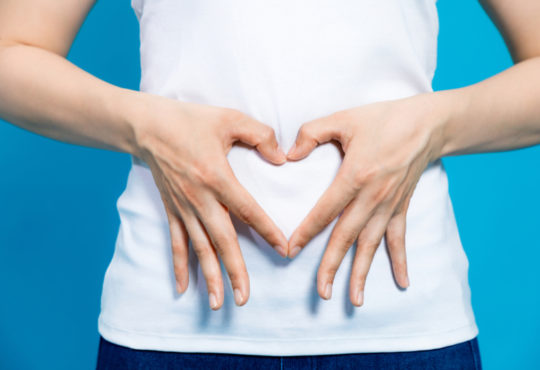 young woman who makes a heart shape by hands on her stomach symbolizing gut health with probiotics